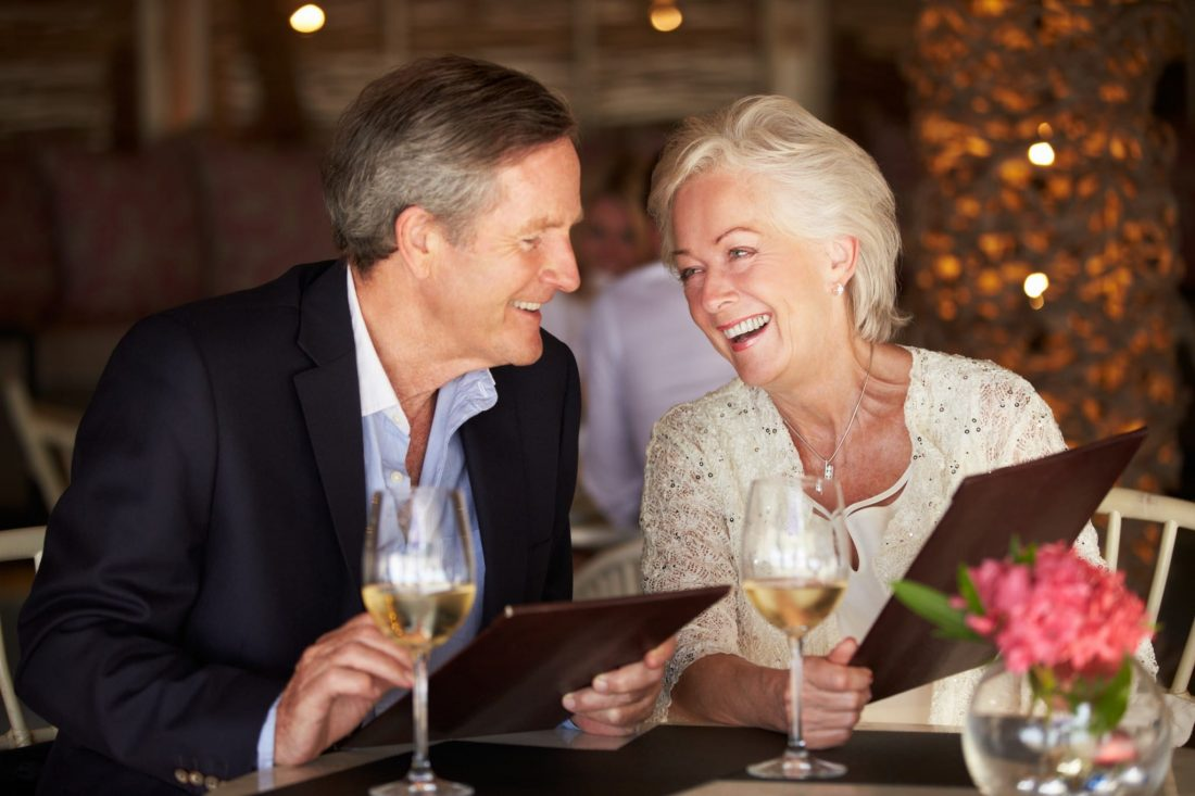 Senior Couple Choosing From Menu In Restaurant Chatting To Each Other Smiling